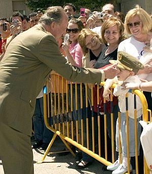 El Rey coloca su gorra a un niño, durante la visita a la Guardia Civil. (Foto: EFE)