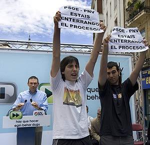 Dos de los jóvenes exponen sus carteles frente al lehendakari, Ibarretxe. (Foto: Iñaki Andrés)
