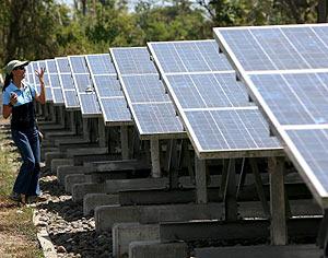 Una mujer junto a varios paneles solares. (Foto: EFE)