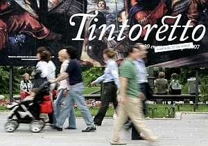 Un grupo de personas pasa por delante de un cartel que anuncia la exposición de Tintoretto. (Foto: EFE)
