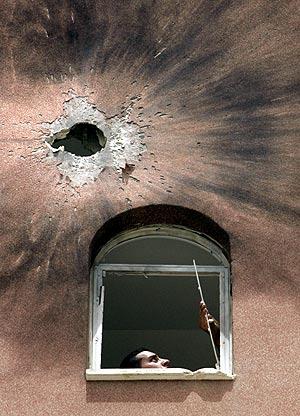 Un palestino mira los daños que ha producido en su casa uno de los ataques. (Foto: AP)