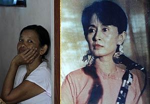 Una mujer sentada a lado de un póster de la líder opositora. (Foto: REUTERS)