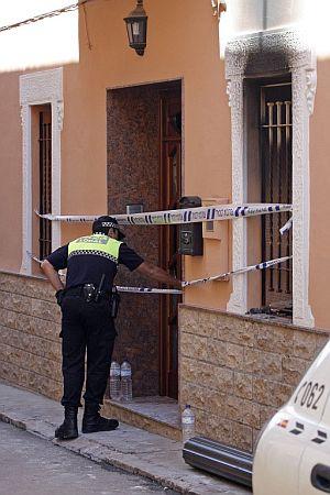 Un agente de la Policía Local observa el interior de la vivienda donde se registró el incendio. (Foto: EFE)