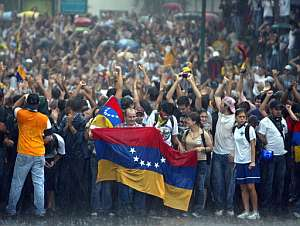 Un grupo de manifestantes contra el cierre de RCTV, protesta bajo la lluvia en Caracas. (Foto: AFP)