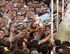Un peregrino lanza a un niño para acercarlo a la Virgen del Rocío. (Foto: AFP)