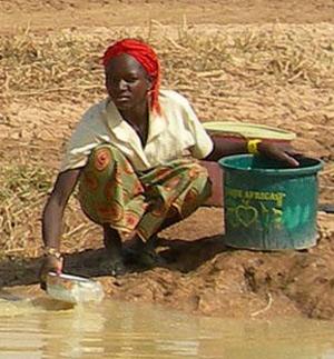 Una mujer africana recoge agua de un charco embarrado. (Foro: Cruz Roja)
