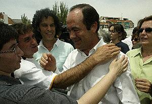 José Bono saluda a varios vecinos en la celebración de la misa en la 'Iglesia Roja'. (Foto: EFE)