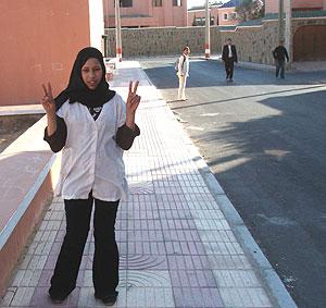 Una niña hace el símbolo de la victoria. Al fondo, con ropa oscura, los agentes de paisano que se la llevaron. (Foto: Javier G. Lachica)
