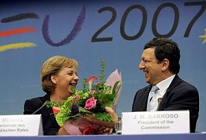 Barroso entrega un ramo de flores a Merkel en la rueda de prensa donde anuncia el acuerdo. (Foto: EFE)