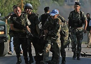 Soldados españoles trasladan el cuerpo de uno de sus compañeros fallecidos. (Foto: AFP)
