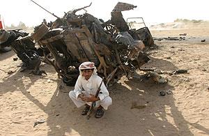 Un yemení custodia los restos de uno de los vehículos afectados por el atentado. (Foto: REUTERS)