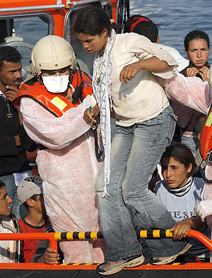 Una mujer abandona una embarcación en el puerto de Málaga.