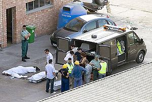 Un momento del traslado de los cadáveres. (Foto: EFE)