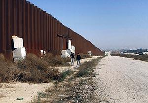 Palestinos caminan cerca del muro de separación construido por Israel. (Foto: AP)