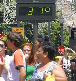 Varios peatones pasean junto a un termómetro que muestra las altas temperaturas. (Foto: Miguel Ángel Molina).