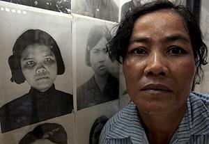 Chim Math posa junto a una fotografía suya en Tuol Sleng. (Foto: EFE)