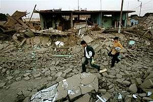 Dos personas rescatan algunas pertenencias de sus casas destruidas. (Foto: AP)