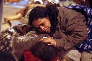 Una mujer llora sobre su hijo herido en Pisco. (Foto: AFP)