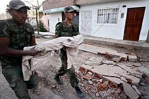 Dos soldados trasladan el cadáver de un niño en Pisco. (Foto: AFP)
