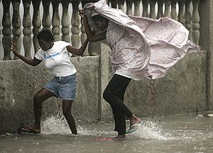Dos mujeres andan con dificultad en Haití entre el viento y la lluvia. (Foto: REUTERS)