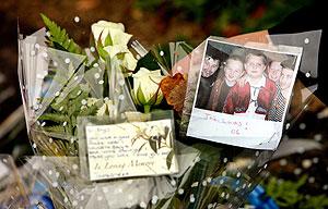 Una foto de Rhys Jones junto a sus amigos en un ramo de flores despositado en el lugar de su muerte. (Foto: AFP)