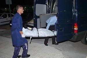 Empleados de una funeraria trasladan el cuerpo de la mujer. (Foto: EFE)