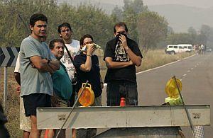 Unos vecinos castellonenses observan el incendio forestal desde uno de los controles de carretera. (Foto: EFE)