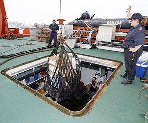 Tripulantes del 'Hespérides' desembarcan las muestras recogidas en el Ártico. (Foto: EFE)