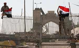 Dos soldados iraquíes colocan banderas de su país en el palacio presidencial de Basora tras ser abandonado por las tropas británicas. (Foto: AP)