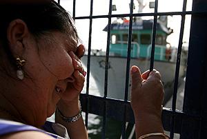 Una vecina de Barbate espera noticias en el puerto. (Foto: AFP)