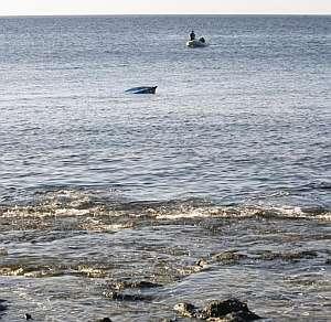 La proa de la patera sobresale del mar a pocos metros de tierra firme. (Foto: EFE)