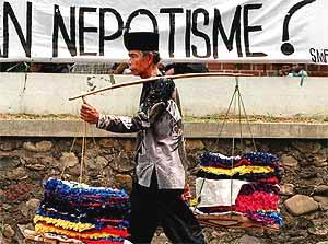 Un vendedor ambulante de Yakarta pasa delante de una pancarta en la que se denuncia el nepotismo de las autoridades. (Foto: AFP)