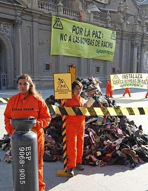 Activistas de Greenpeace junto a una montaña de zapatos que representa a las víctimas de las bombas de racimo. (Foto: EFE)