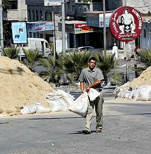 Un palestino carga sacos para proteger posiciones de la franja de Gaza. (Foto: AP)