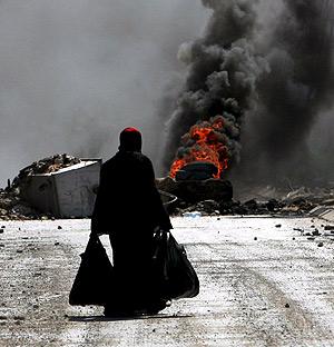 Una iraquí huye del campo de refugiados de Al Ain tras un ataque. (EFE)