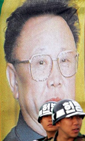 Dos militares surcoreanos frente a un cartel con la imagen del dictador norcoreano, Kim Jong-il. (Foto: AP)