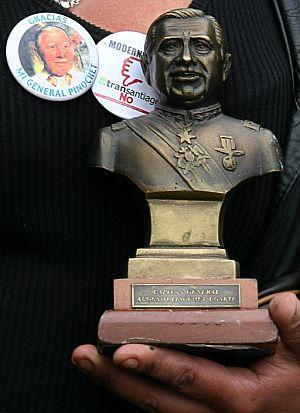 Una seguidora de Pinochet muestra un busto del ex dictador. (Foto: EFE)