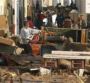 Un hombre retira muebles de su casa en El Vergel. (Foto: AP)