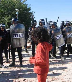 Una niña con una pelota de goma antidisturbios observa a los agentes. (R. Bécares) MÁS FOTOS