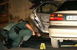 Efectivos de la Guardia Civil buscan pistas en el coche donde el alcalde fue tiroteado. (Foto: EFE)