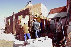 Vecinos reconstruyendo la casa derribada por orden judicial. (Foto: Julio Palomar)