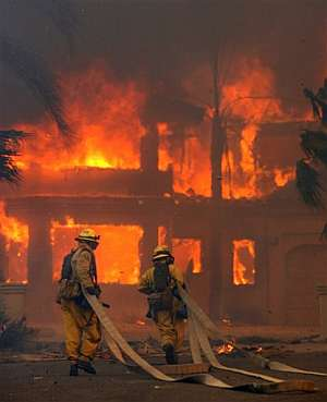 Los bomberos llegan con sus mangueras a una casa devorada por las llamas en Poway, California. (Foto: AP)