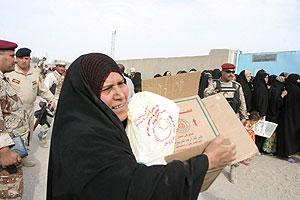 Una mujer iraquí transporta la ayuda humanitaria en el sur de Bagdad. (Foto: EFE)