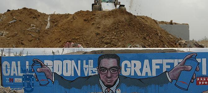 Arriba, una excavadora echa tierra sobre el grafiti de Gallardón; abajo, el grafiti. (Desviados.com/R.B.)