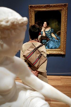 Una visitante contempla uno de los retratos de la muestra. (Foto: S. Sánchez)