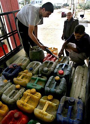 Un palestino reparte bidones de combustible en Rafah. (Foto: AFP)