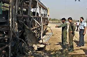 Varios oficiales examinan los restos del autobús militar que sufrió un atentado suicida en Sargodha. (Foto: AP)