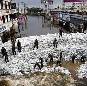 Soldados tratan de hacer una barrera con sacos para frenar el paso del agua. (Foto: AP)