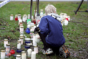 Un niño coloca una vela cerca de la escuela de Tuusula. (Foto: EFE)
