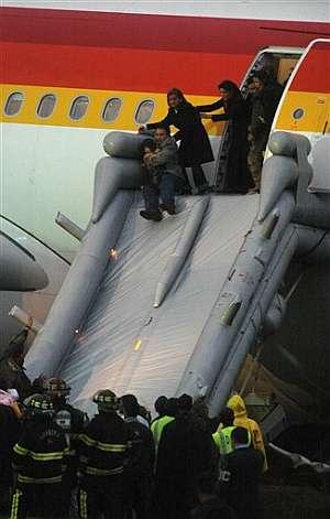 Un pasajero desaloja el avión con su hijo en brazos. (Foto: AP)